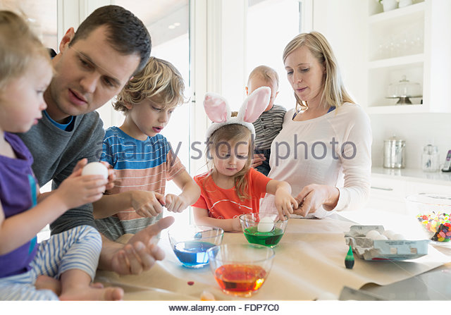 Family dipping Easter eggs in food coloring - Stock-Bilder