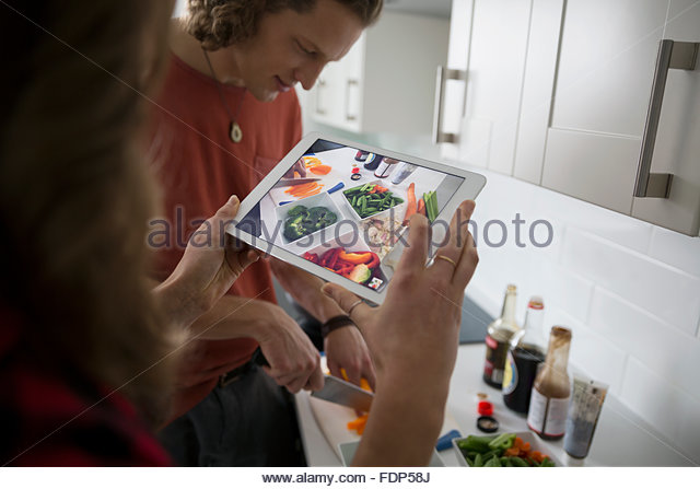Couple cooking photographing with digital tablet in kitchen - Stock Image