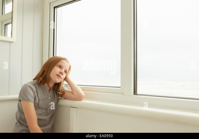 Portrait of girl gazing out of holiday apartment window - Stock Image