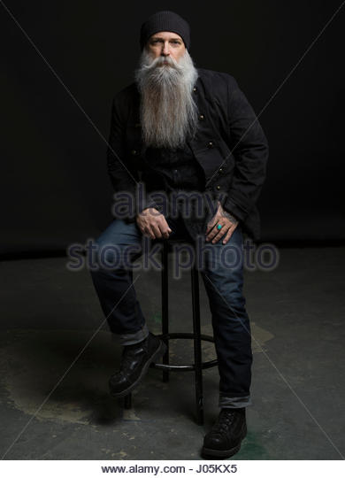 Portrait confident hipster man with long gray beard on stool against black background - Stock Image
