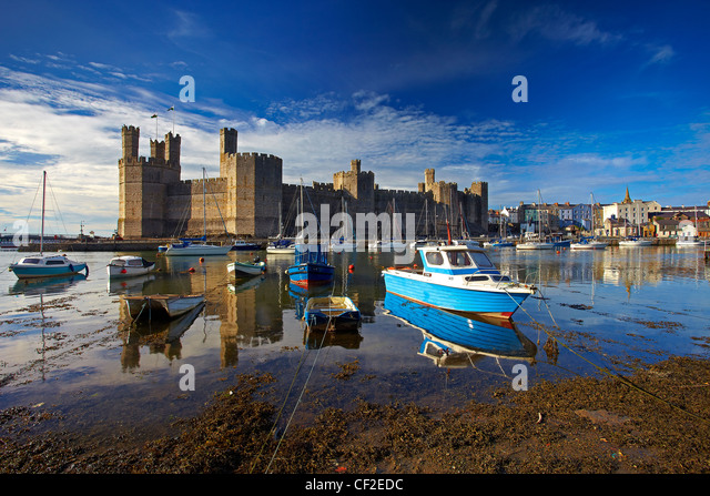 Boats moored by Caernarfon Castle at the mouth of the of the Seiont river. - Stock Image