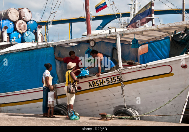 Woman buying fish at the Floating Market on the Punda side of Willemstad, Curacao - Stock Image
