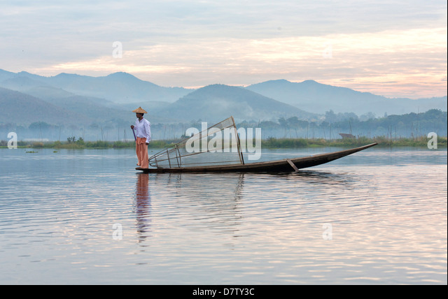 Intha leg rowing fishermen at sunset on Inle Lake, Inle Lake, Shan State, Burma - Stock Image