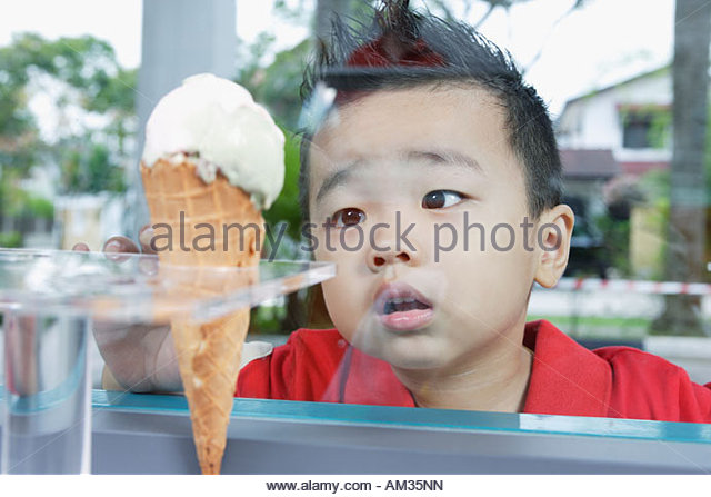 Boy looking at ice cream cone through glass - Stock Image