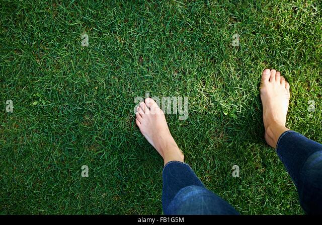 Woman standing on grass, low section, elevated view - Stock Image