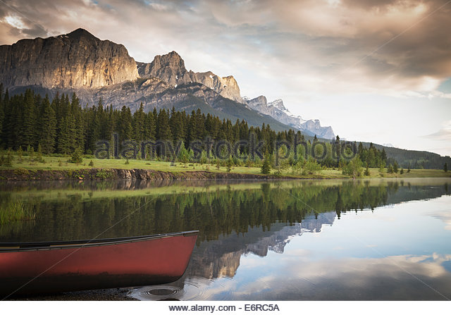 Boat on still lake in rural landscape - Stock Image