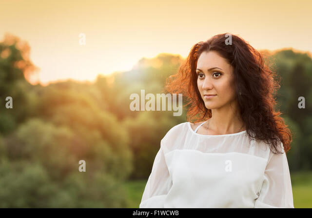Young gorgeous lady in white dress in sunset beams. Beauty woman with dark hair looking aside. Image with copy space. - Stock Image