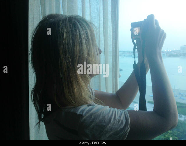 United Arab Emirates, Abu Dhabi, Woman taking photography out of window - Stock Image