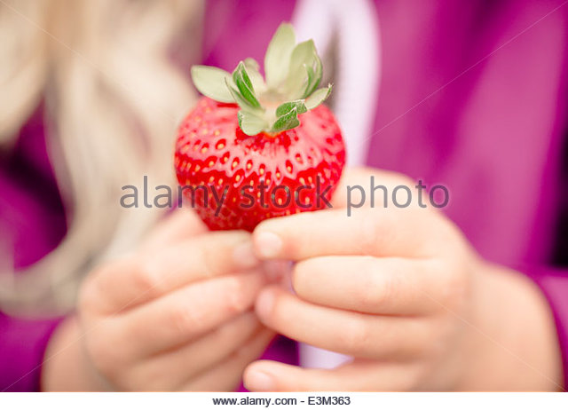 Close-up view of girl (2-3) showing strawberry - Stock Image