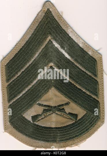 Gunnery Sergeant insignia patch from the Vietnam War, green and tan color, featuring two crossed rifles, 1964. - Stock Image