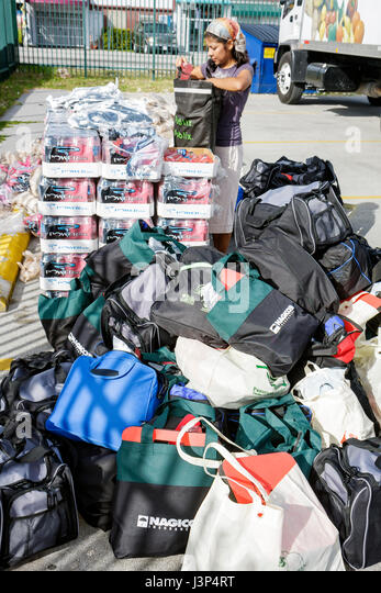 Miami Florida Little Haiti Thanksgiving Turkey Give-Away give away volunteers Black Haitian woman packing bags assistance - Stock Image