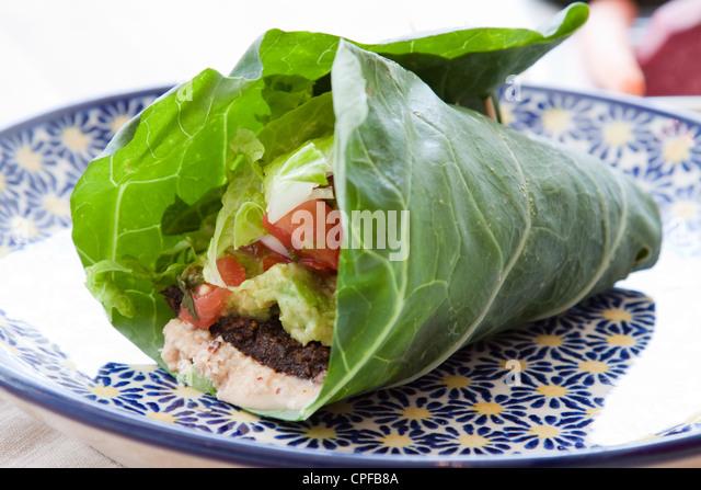 Seasoned nut loaf, guacamole, romaine lettuce, salsa & almond nut cheese wrapped in a collard leaf. - Stock-Bilder