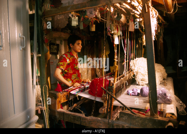 Man Weaving Carpet Algeria - Stock Image