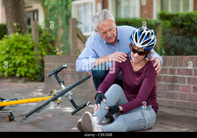 Cycling accident. Man helping a cyclist that has fallen from her bike. - Stock Image