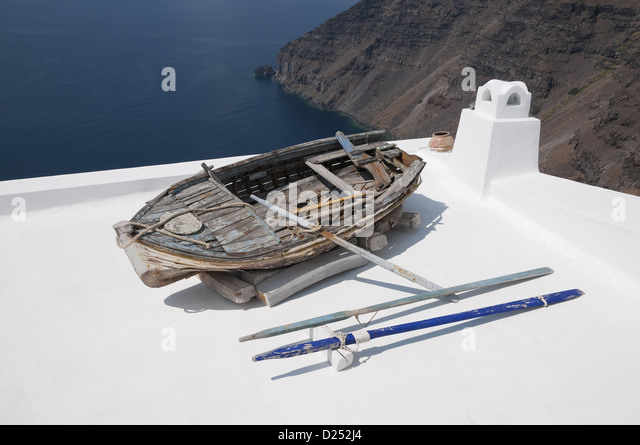 Old weathered rowing boat on house roof terrace, Fira, Santorini, Cyclades, Aegean Sea, Greece, September - Stock Image
