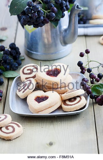 Black-and-white biscuits and heart-shaped biscuits with aronia jam - Stock Image