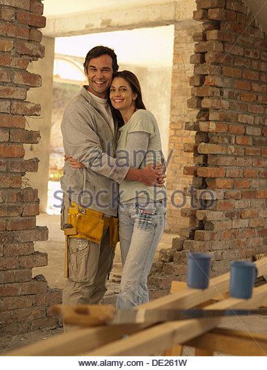 Couple hugging in doorway of house under construction - Stock Image