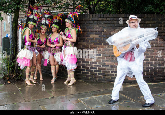 Dancers from the Paraiso School of Samba take shelter from the rain before the Notting Hill Carnival parade, London, - Stock Image