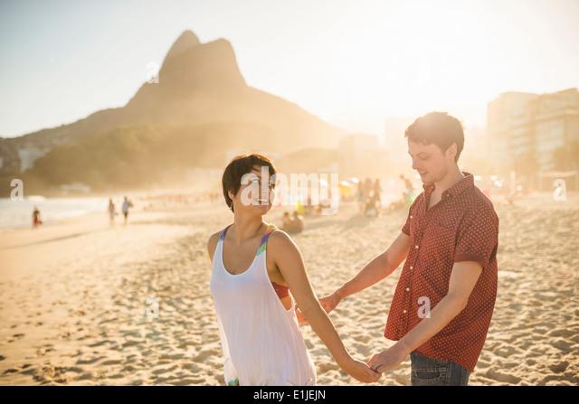 Young couple enjoying sunset, Ipanema Beach, Rio, Brazil - Stock-Bilder
