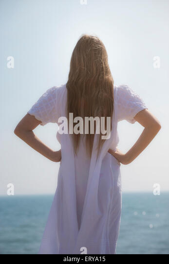 a girl in a white dress from behind - Stock Image
