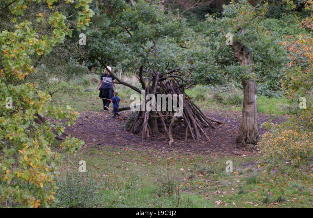 Mother and child playing around a den in the woods - Stock Image