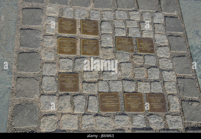 Stolpersteine are concrete blocks which are laid into the pavement in front of the last voluntarily chosen places - Stock Image