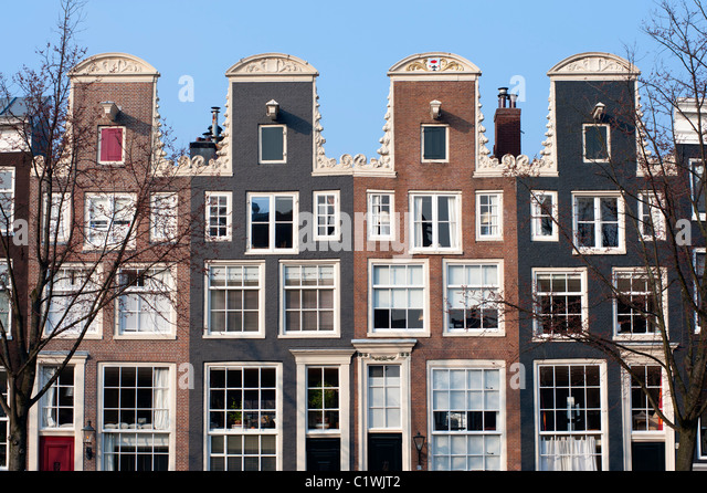 Traditional historic Dutch gable houses beside canal in Amsterdam The Netherlands - Stock Image