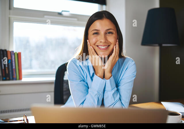 Happy young businesswoman working from home sitting resting her chin on her hands looking at the camera with a beaming - Stock Image
