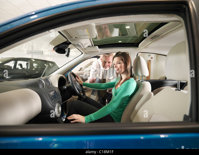 Salesman shows customer a car - Stock Image