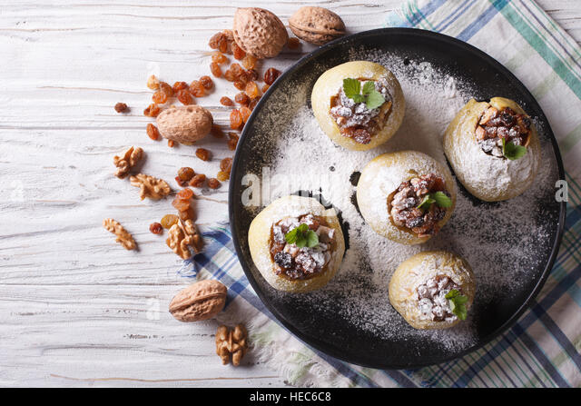 Homemade baked apples with raisins, walnuts and honey on a plate horizontal view from above - Stock Image