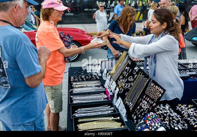 Miami Beach Florida Art Deco Weekend community festival vendor stall shopping display jewelry jewellery Asian woman - Stock Image