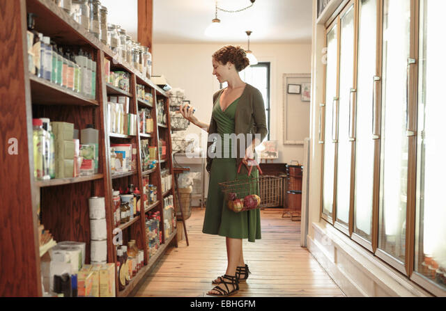 Female customer selecting from shelf in country store - Stock Image