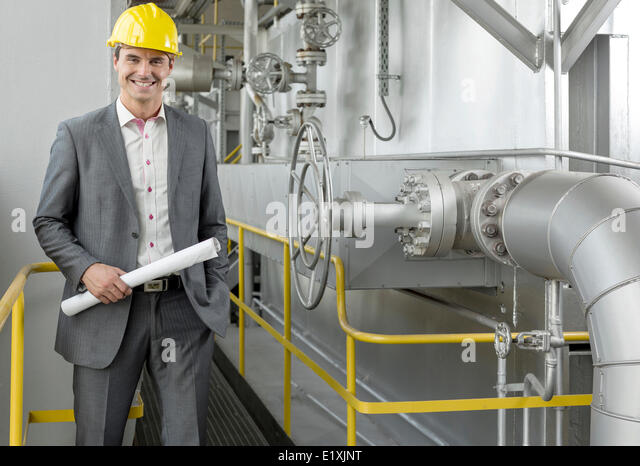 Portrait of confident young male architect holding blueprint by machinery in industry - Stock Image