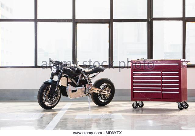 Electric cafe racer motorbike in garage - Stock Image