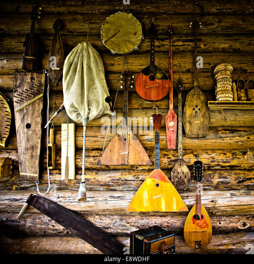 Folk musical instruments. Exotic ancient folk musical instruments on the log wall - Stock Image