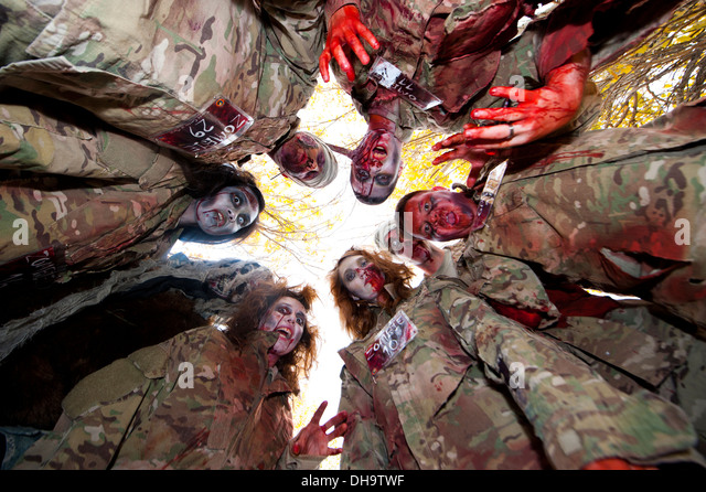 Zombies made of simulated undead military prepare to eat their latest victim at Transit Center at Manas, Kyrgyzstan, - Stock Image