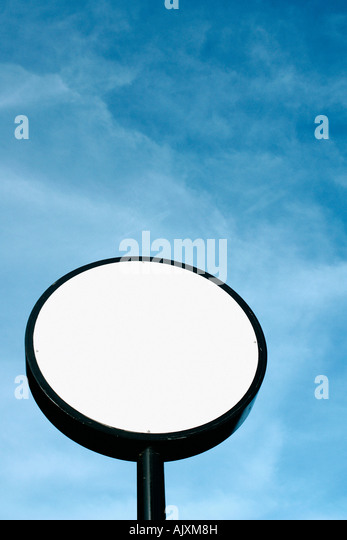 Circular White Sign on a Pole Against a Clear Blue Sky on a Sunny Day with Copy Space - Stock Image