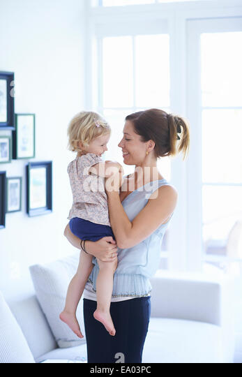 Mid adult woman and toddler daughter in living room - Stock Image