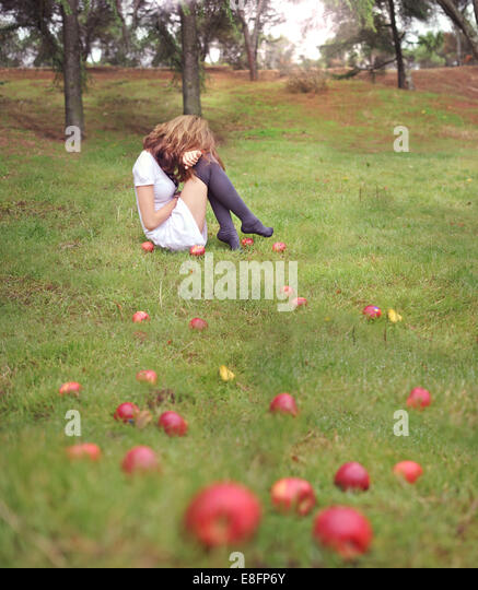 Woman sitting on grass in an apple orchard - Stock Image