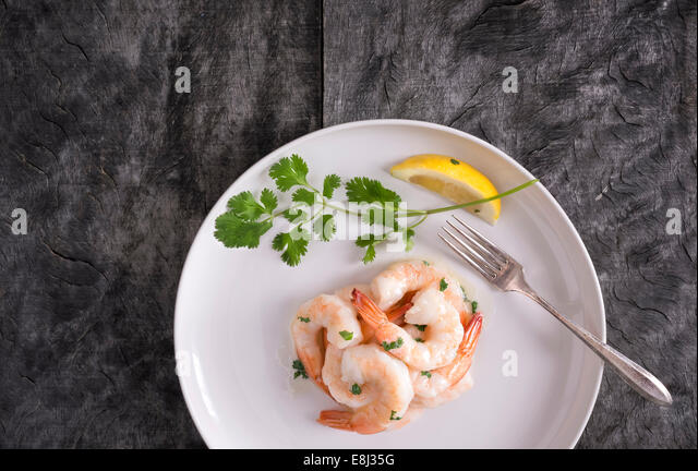 Shrimp on white plate with butter and herb sauce. Set on a rustic gray wood surface with antique fork. - Stock Image