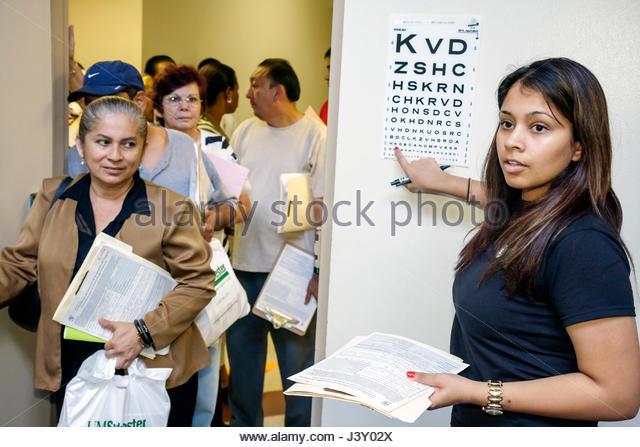 Miami Florida Liberty City Jessie Trice Community Health Center fair free care exam volunteer Hispanic woman ophthalmology - Stock Image