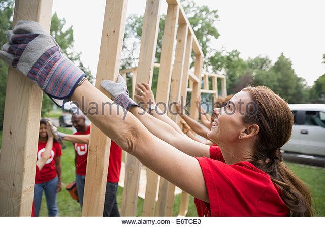 Smiling volunteers lifting construction frame - Stock-Bilder