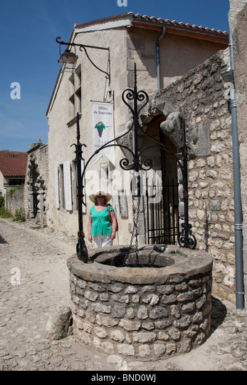 A well in the middle of a medieval village in the Auvergne, France. - Stock Image