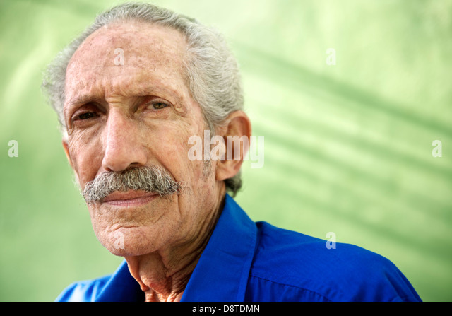 Elderly people and emotions, portrait of serious senior caucasian man looking at camera against green wall - Stock-Bilder