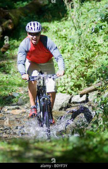 Mountainbiker crossing water - Stock Image