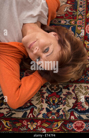 High angle view of relaxing senior woman lying on floor, Munich, Bavaria, Germany - Stock-Bilder