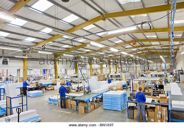 Workers on production line in factory that manufactures aluminium light fittings - Stock Image