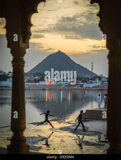 Boy leaping over puddle near the sacred Lake during Pushkar Camel fair. - Stock-Bilder