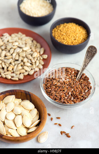 Assorted oil seeds (flax, sesame, pumpkin, sunflower, mustard) in small bowls on stone background - organic ingredients - Stock Image