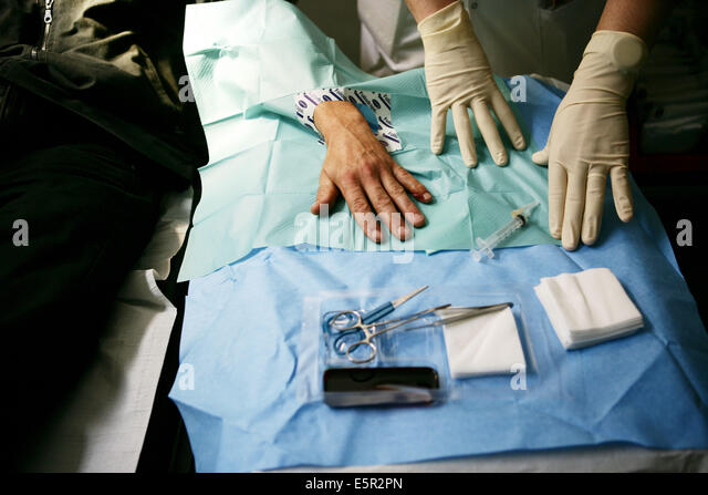 Doctor stitching up the hand of a patient, Emergency Department, Lariboisière Hospital, Paris, France. - Stock Image